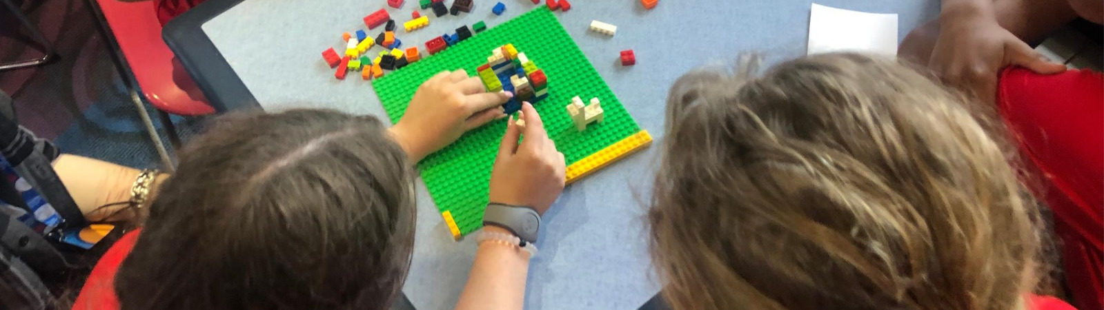 Students working together on a lego project sitting around a table