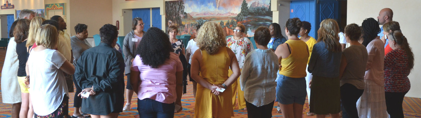 Educators gathered in a circle during a Pegasus Springs Education Collective event