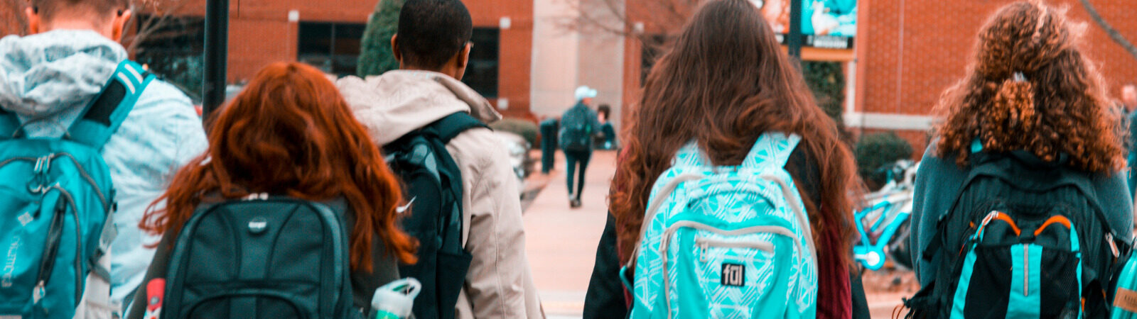 Students walking into school, image from behind so you can only see back of their heads and backpacks